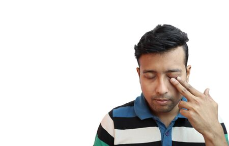 indonesian guy weeping in depressed mood with finger on eye in white background with copy space for text.Sad mood concept Reklamní fotografie