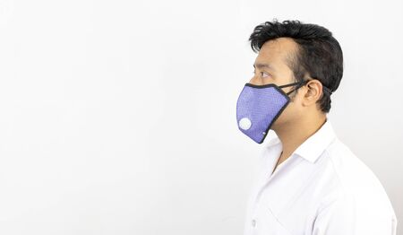 a male medical professional in white coat and mask in white background. view from left. concept image for viral infection precaution Reklamní fotografie