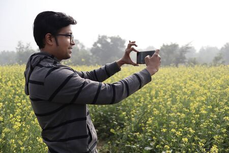 a man in hoodie and spectacles clicking nature photo with his smartphone in a mustard field with yellow blossomed mustard flowers during day time Reklamní fotografie