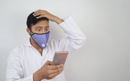 a male doctor with mask and white coat shocked to see a news in his mobile phone in hand isolated in white grey background with copy space for text