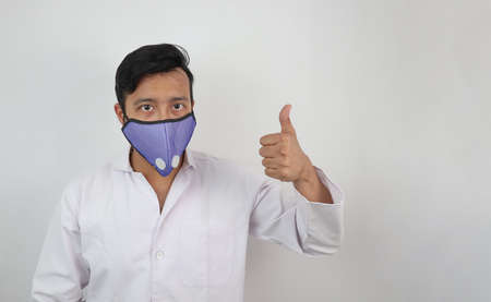a medical professional in white coat and n 99 mask with thumbs up positive expression isolated in white background with space for text. Фото со стока