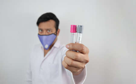 a medical professional in white coat and n 99 mask with vials in hand in white background with space for text.