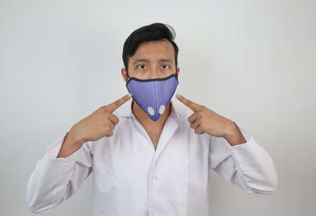 a medical professional in white coat and n 99 mask pointing towards the mask in white background with space for text. Фото со стока