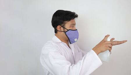 a male doctor in mask and white coat demonstrating use of hand sanitizer. Hand washing protocol