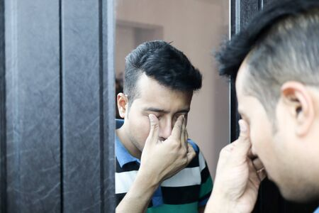 a man with head down in front of a mirror in depressed mood with selective focus on mirror image