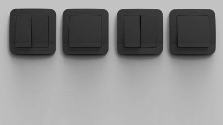 3d render of black plastic switches panel on a gray wall Archivio Fotografico