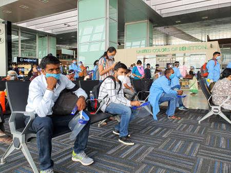 6th June 2020- Netaji Subhas Chandra Bose International Airport, Calcutta, India-Travelers maintaining social distancing in protective gear before boarding flight at airport. Editoriali