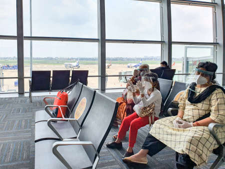 6th June 2020- Netaji Subhas Chandra Bose International Airport, Calcutta, India-Family members maintaing social distancing in protective gear before boarding flight at airport.