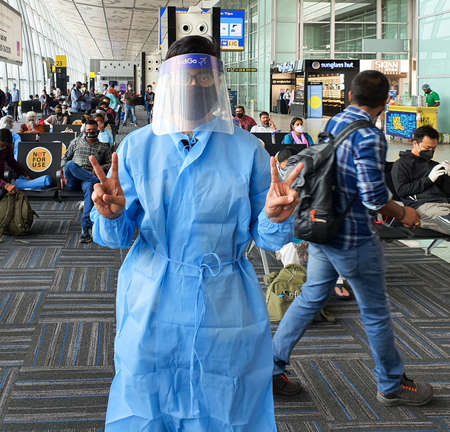 6th June 2020- Netaji Subhas Chandra Bose International Airport, Calcutta, India-A traveller wearing full body suit and face shield provided by Indigo airlines at Calcutta Airport. Редакционное