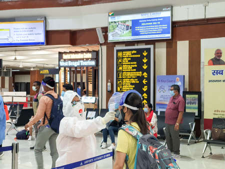 6th June 2020- Bagdogra Airport,Siliguri, West Bengal, India-Passengers in protective gear being themal scanned for covid screening by airport crew at Bagdogra airport. Редакционное