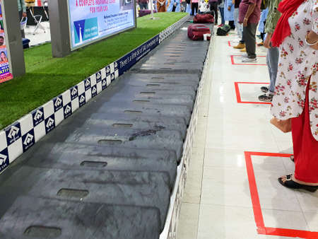 6th June 2020- Bagdogra Airport,Siliguri, West Bengal,India -Travelers collecting baggage from baggage belt maintaining social distancing by standing in red marked areas. Редакционное