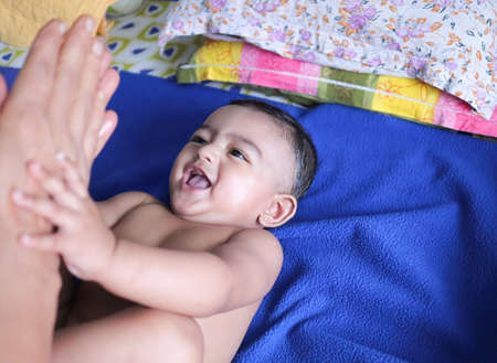 an infant toddler baby boy smiling on a blue towel Фото со стока