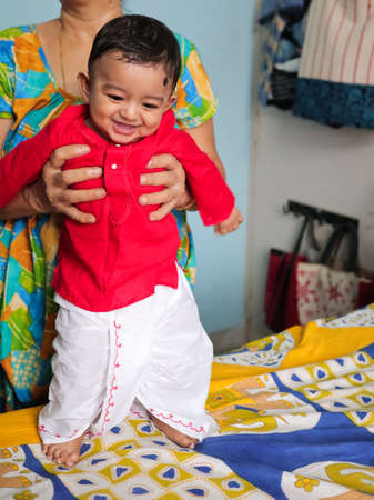 an infant indian toddler boy dressed in traditional indian dhoti kurta bengali cultural dress