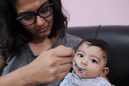 an indian mothher feeding milk to a baby boy with a spoon Фото со стока