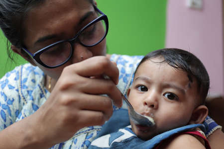 an infant toddler baby boy after weaning eating solid food with spoon