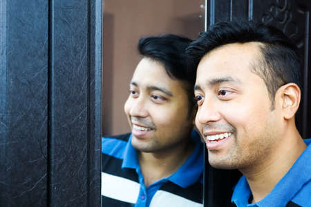 a man i and his reflection in mirror smiling in happy mood Фото со стока