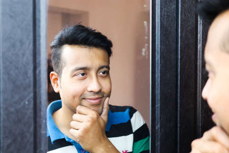 a confident man looking at his reflection in mirror and making smile gesture