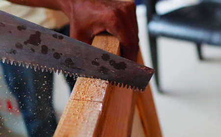 An wooden door being cut by a saw manually