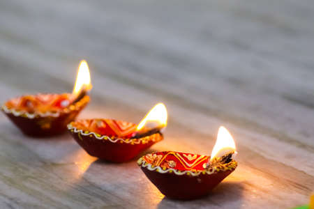 a set of 3 earthen oil lamp being lit at a temple during worship