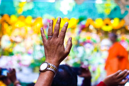 a devotee raising hands in a temple with blurred background and selective focus