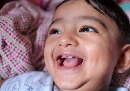 close up photo of an indian baby boy with first tooth erupted and giving a gummy smile