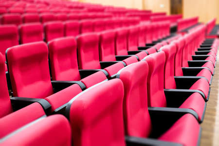 empty rows of seats of an auditorium with red reclining rows of seats and false ceiling led lights