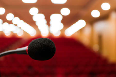 close up photo of a microphone with blurred background & bokeh lights of auditorium with selective focus on microphone Stage mic fear concept image Standard-Bild