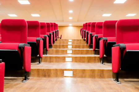 stairscase gallery between empty rows of seats of an auditorium with red reclining rows of seats and false ceiling led lights