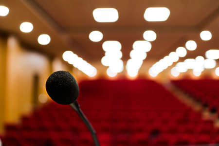 close up photo of a microphone with blurred background & bokeh lights of auditorium with selective focus on microphone Stage mic fear concept image Stock Photo