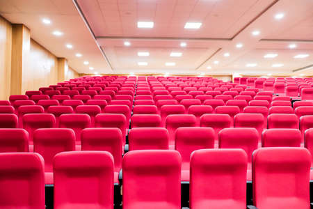 empty seats of an auditorium with red reclining rows of seats and false ceiling led lights