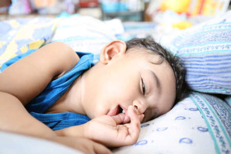 an adorable indian baby with one tooth sleeping with finger in mouth