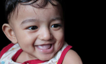 a portrait of an adorable indian baby looking at downwards and right with selective focus on front eye with copy space in black background