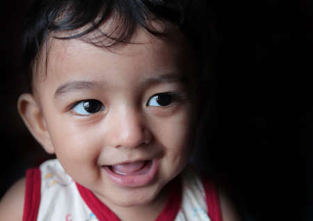 a head shot portrait of an adorable indian baby looking at right with selective focus on front eye with copy space in black background