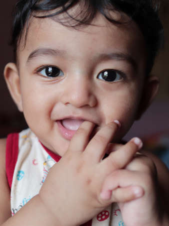 a head shot vertical portrait of an adorable indian baby looking at the camera with selective focus on eyes