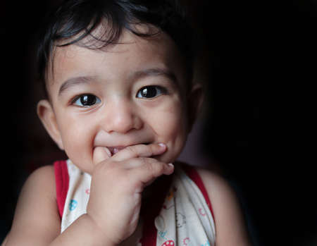a head shot portrait of an adorable indian baby looking at the camera with selective focus on eyes with black background