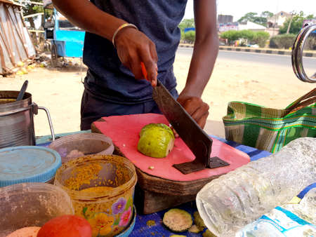 picture of vendor cutting guava with blade for making chaat with gren chilly paste, red chilli powder, chat masala, salt, black salt and lemon