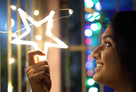 close up portrait of a lady smiling and holding neon star light with bokeh background. Selective focus on face. Diwali festival concept image Stock Photo
