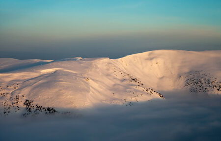 Peaks above clouds, winter mountains, foggy morning photo