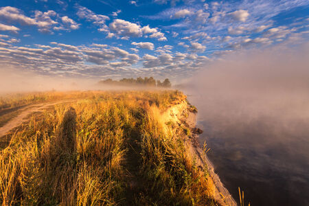 beautiful summer landscape misty morning on the river and clouds reflected in water