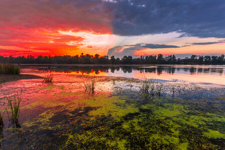inlet bay: Amazingly colorful sunset with reflective red sand and bright clouds Stock Photo