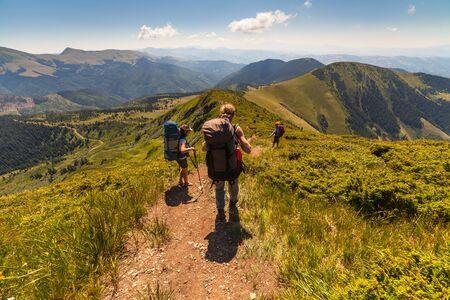 actividad fisica: Un grupo de personas con mochilas caminando a lo largo de la carretera en la monta�a