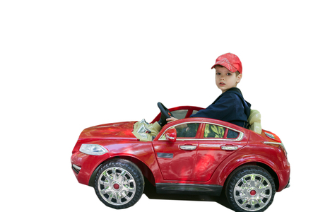 rides: boy rides a red car isolated on a white background. Stock Photo