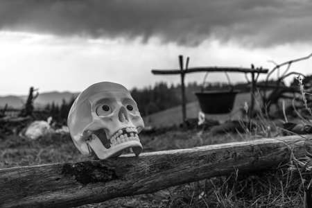 strange mountain: skull on the bench against the backdrop of the mountains. bw