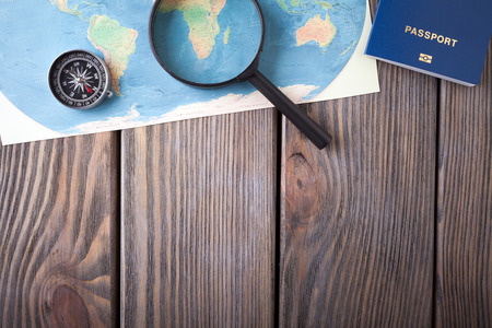 Preparation for Traveling concept, passport, compass, map on a wooden background