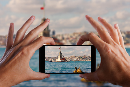 Travel concept. Hand making photo of city with smartphone camera. Istanbul. Turkey.
