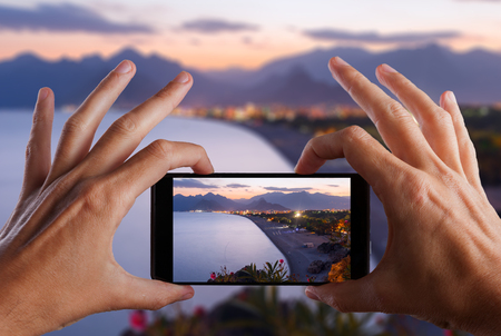 Travel concept. Hand making photo of city with smartphone camera. Antalya . Turkey Stock Photo