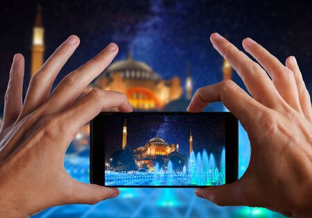 Travel concept. Hands making photo of night city with smartphone camera. Istanbul at nighte. Turkey
