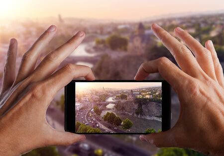 Travel concept. Hands making photo of TBILISI capital of Georgia. Stock Photo