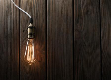 The light bulb illuminates on wooden background