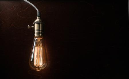 The light bulb illuminates on dark wooden background Фото со стока